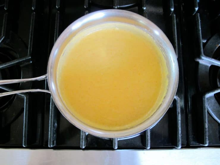 Whisking milk into a roux in a saucepan.