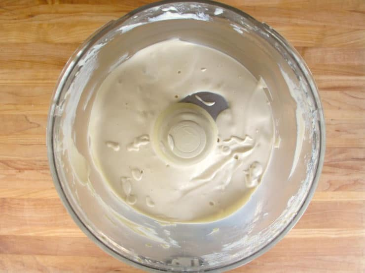 Blending tahini paste, water, lemon juice and salt in a food processor.