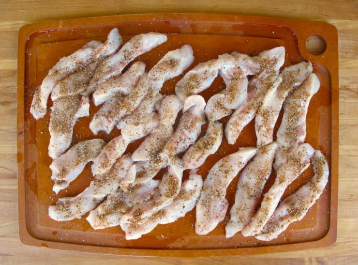 Catfish fingers on a cutting board.