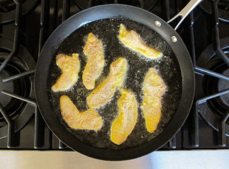 Frying catfish fingers in a skillet.