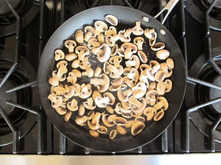Sliced mushrooms sauteeing in a skillet.