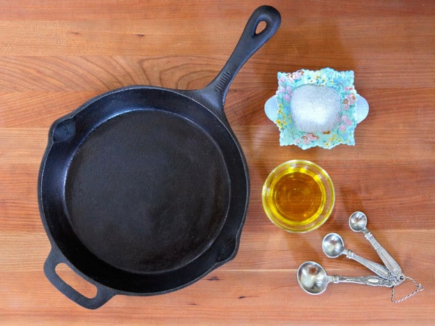 Clean seasoned cast iron pan on wooden background with oil, salt and measuring spoons on the side.