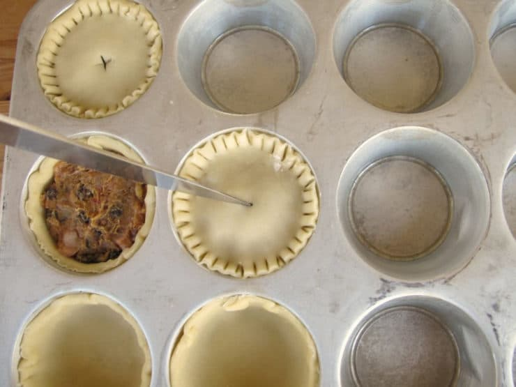 Cutting a vent in the top of mini pies.
