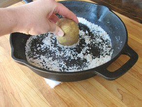 Hand rubbing potato half against salt in cast iron pan.