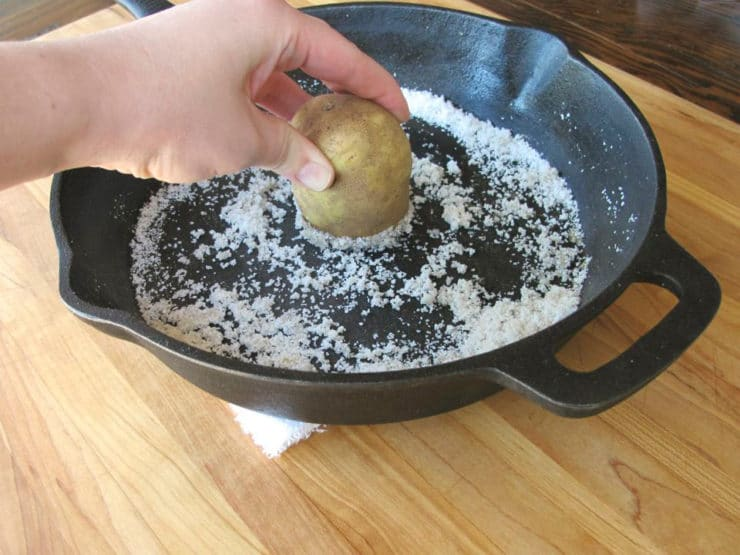 Hand rubbing potato half against salt in cast iron pan.