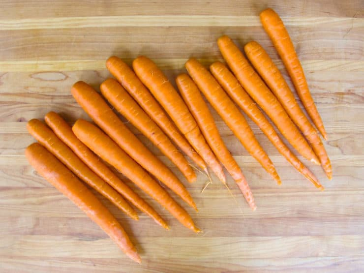 Washed carrots on a cutting board.
