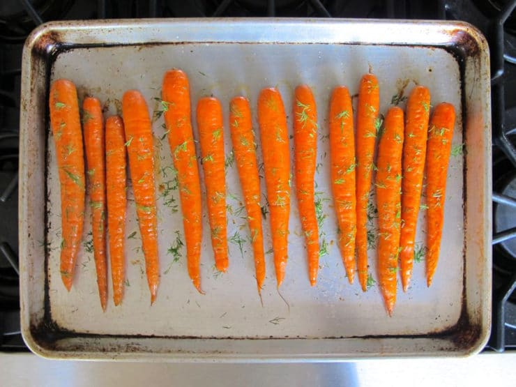 Carrots on a baking sheet with oil and dill.