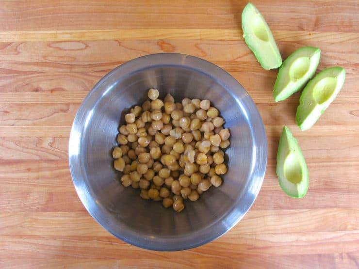 Sliced avocado next to a bowl of chickpeas.