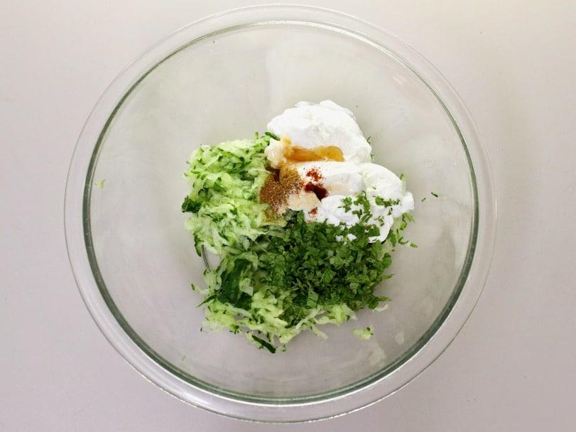 Horizontal shot - glass mixing bowl filled with cucumber raita ingredients.