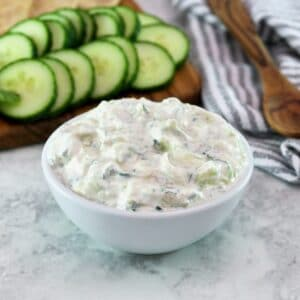 Horizontal shot - white bowl of cucumber raita with cucumber slices in the background.