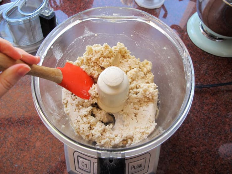 Scraping down the sides of a food processor with a rubber spatula.