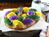 Brightly decorated braided circular King Cake on white parchment with towel in background.