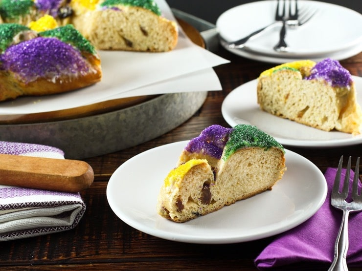 Colorful slice of King Cake on white plate with cake, plate and utensils in background.