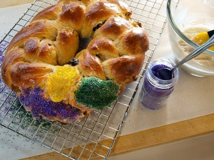 A circular King Cake is being decorated on a wire cooling rack with brightly colored sugar. Nearby sits a container of colorful sugar with a spoon resting inside.