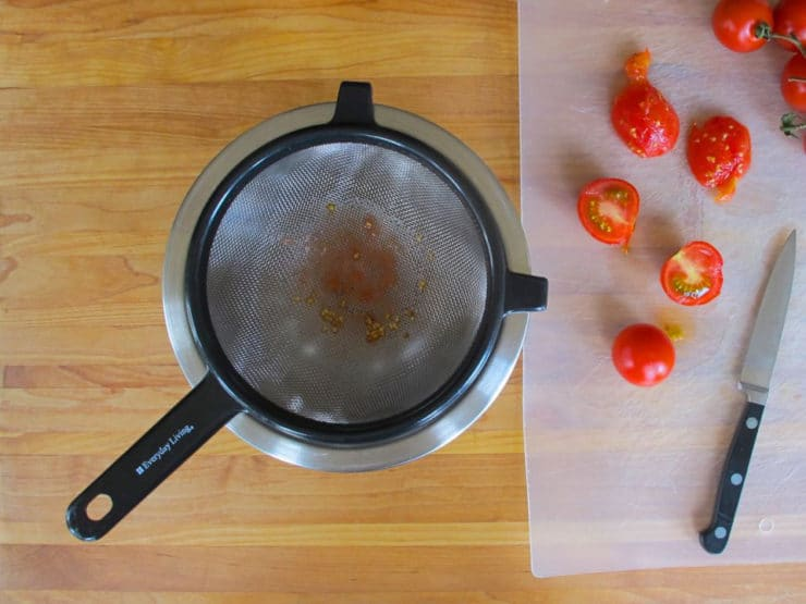 Straining pulp from fresh tomatoes.