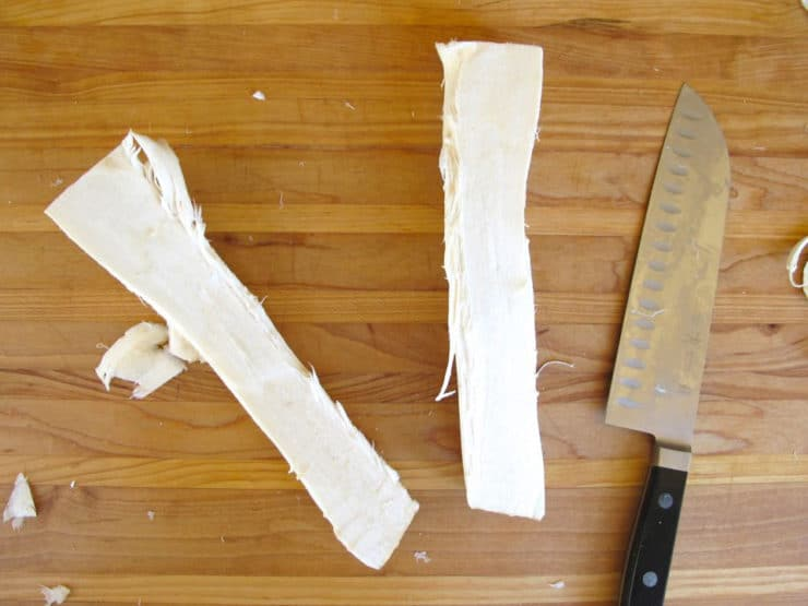 Cutting horseradish to fit in food processor tube.