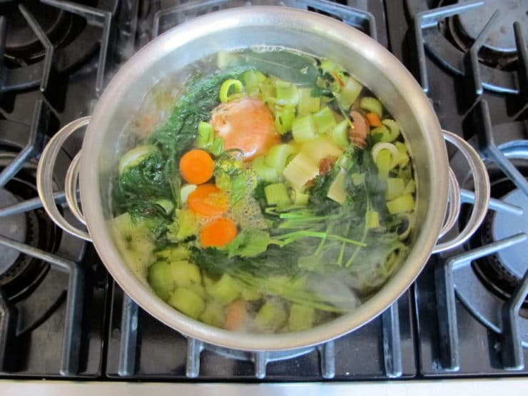 Diced vegetables covered with water in a stockpot.