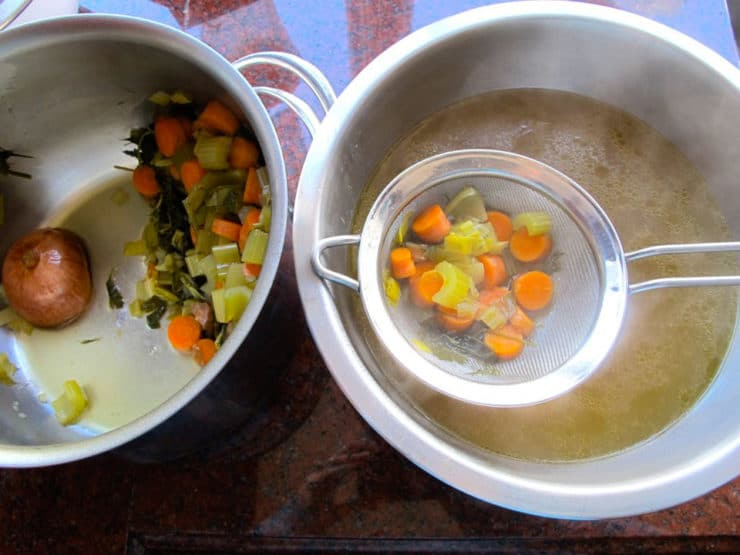Straining vegetables out of chicken stock.