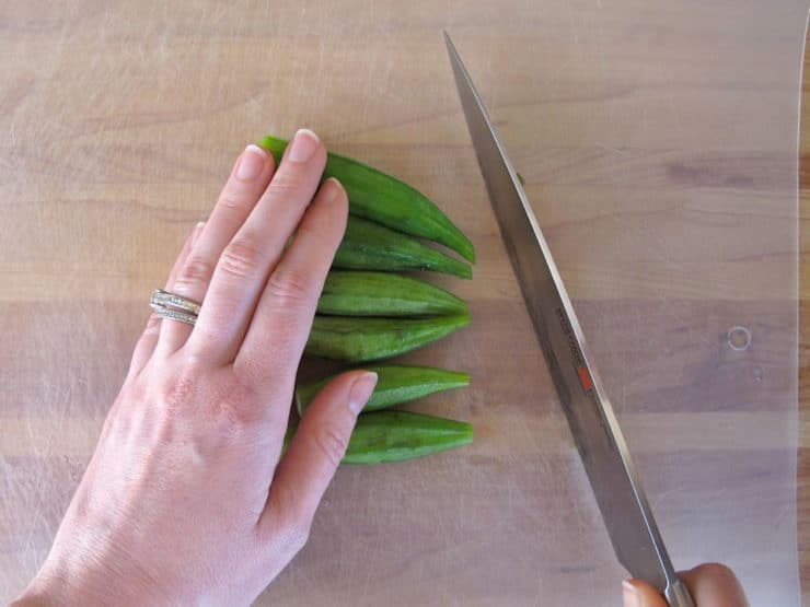 Chopping off pointy end of okra.