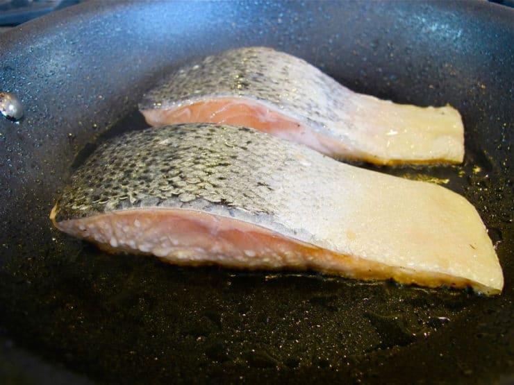 Closeup of salmon searing.
