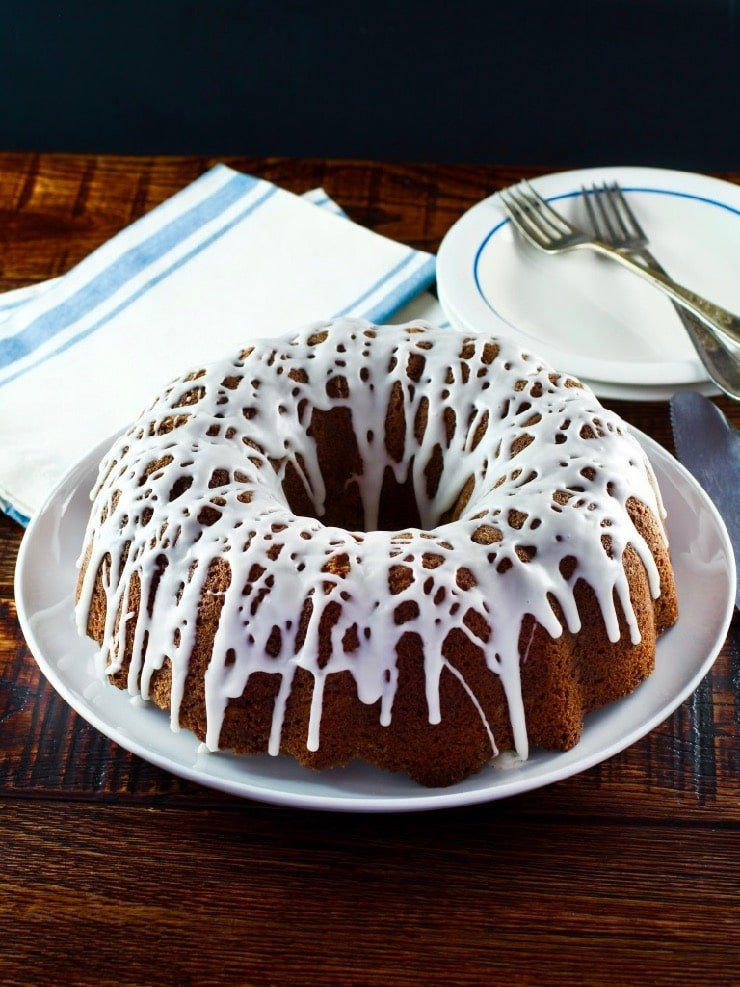Wide shot of sour cream coffee bundt cake drizzled with white icing, napkin, plate and fork in background.