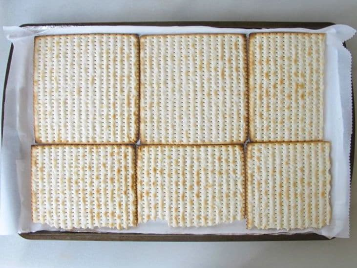 Matzo crackers lining a baking sheet.