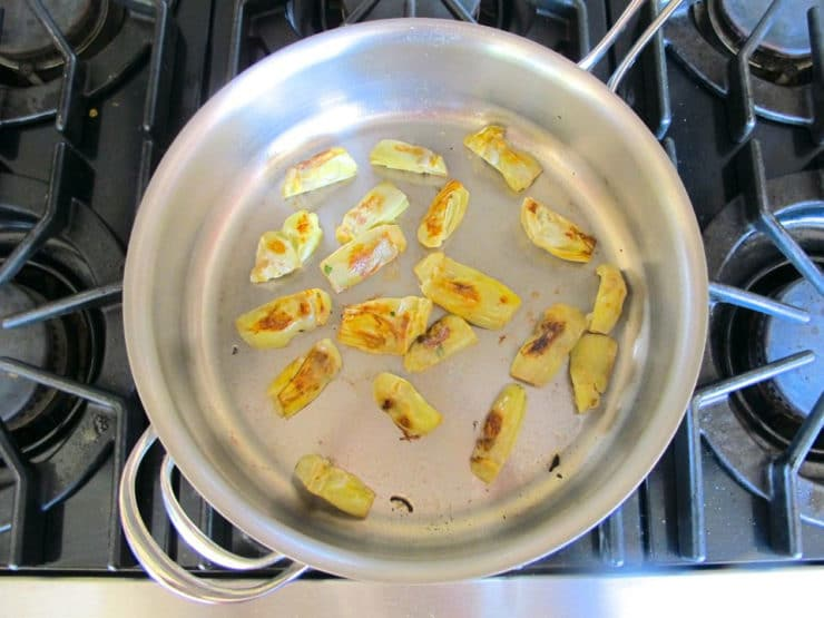 Browning artichokes in a saute pan.