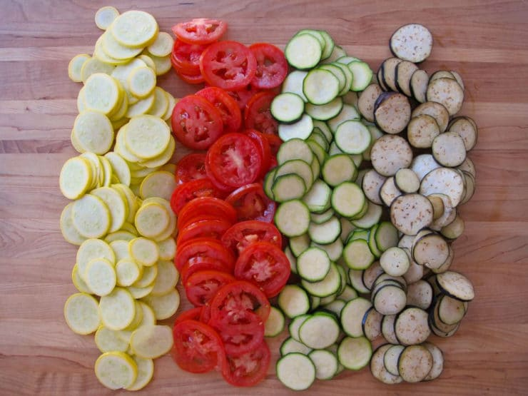 Piles of sliced vegetables on a cutting board.
