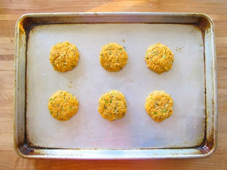 Salmon cakes on a lined baking sheet.