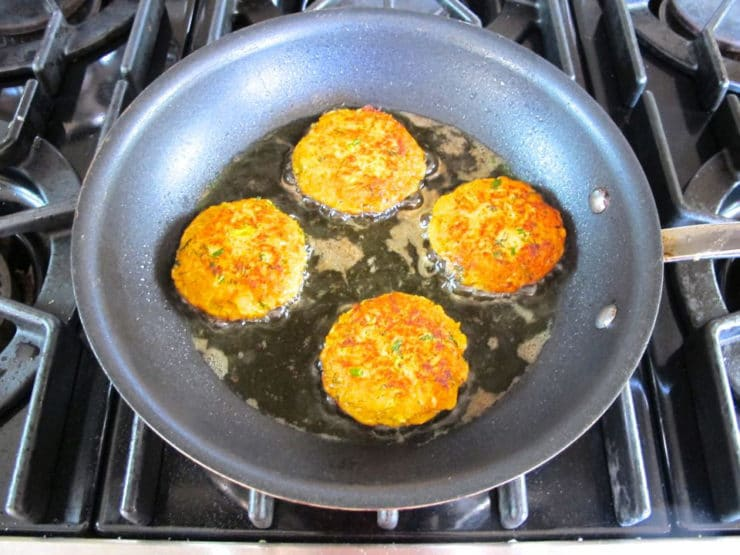 Salmon cakes frying in a skillet.