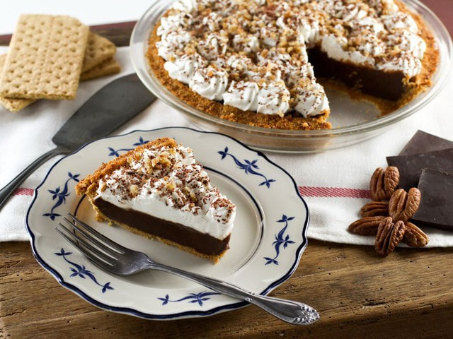 A slice of chocolate icebox pie topped with whipped cream and nuts on a blue plate with a blue border on a wooden table.