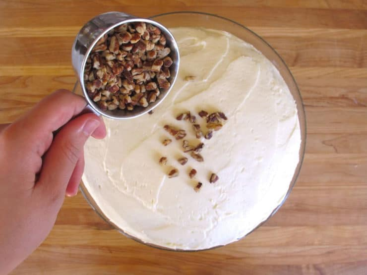 Topping a round cake with nuts.