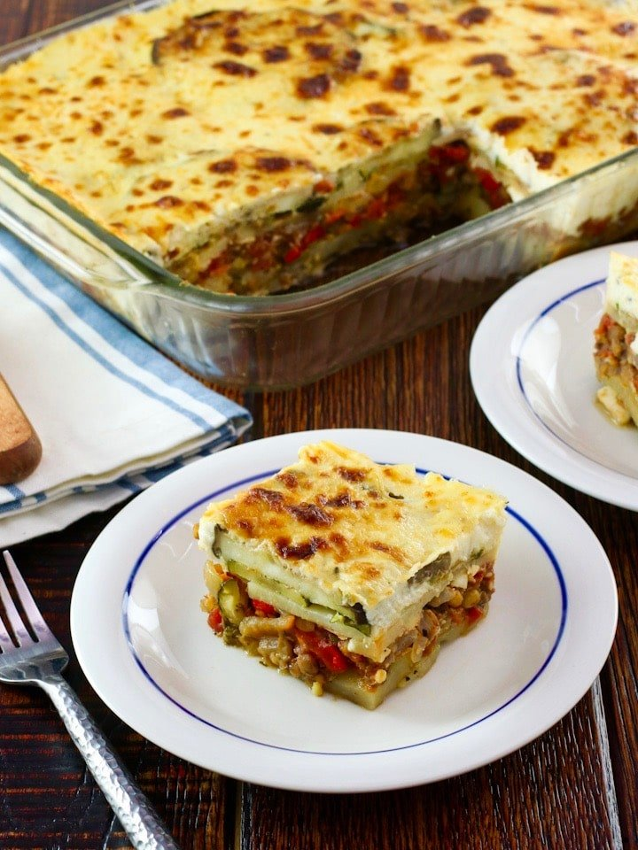 Slice of Roasted Vegetable Moussaka on a small plate in front of casserole dish with moussaka, fork, cloth napkin and serving utensil on wooden tabletop.