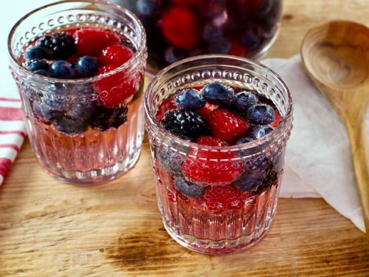 Two decorative glasses of Vanilla Berry Sparking Sangria on a wooden cutting board with wooden spoon, pitcher in background.