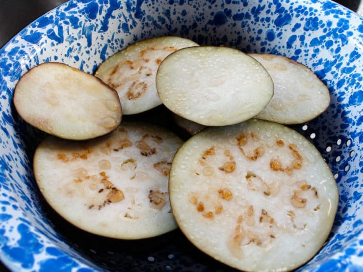 Sliced eggplant rounds in a bowl.