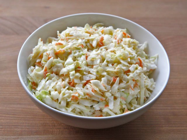 Cole slaw in a white bowl on a wooden table.