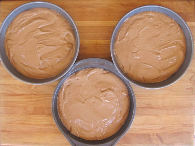 Cake batter divided into three round pans.