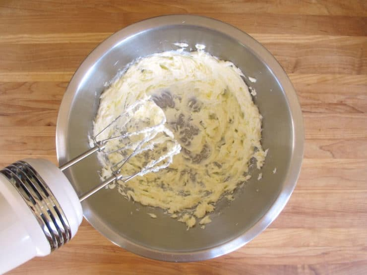 Beating butter in a mixing bowl.