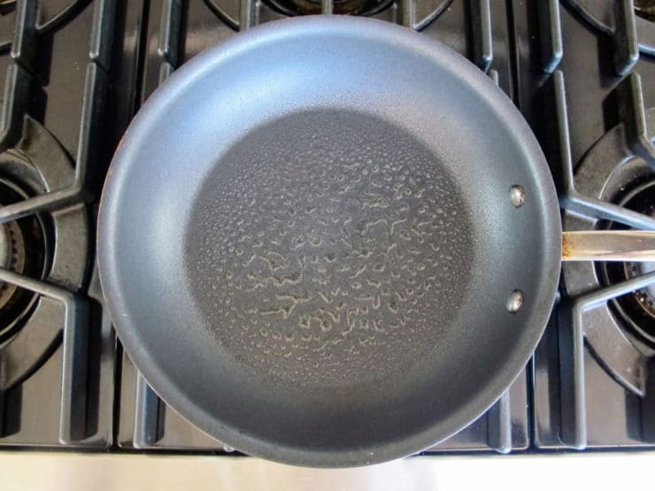 Greasing a preheated nonstick skillet.