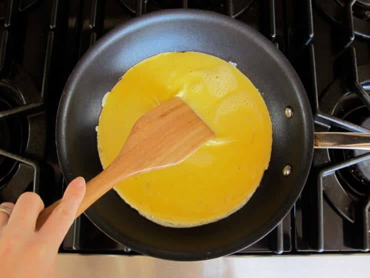 Gently pushing cooked egg to the center of the skillet.