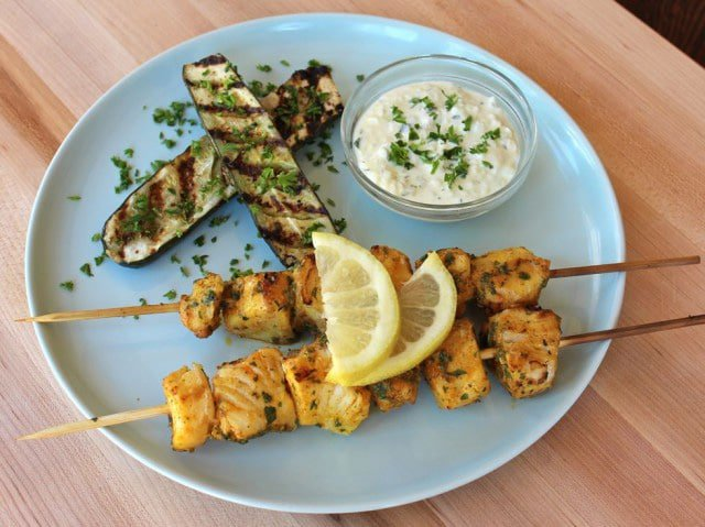 Marinated fish skewers and grilled zucchini on a blue plate on a wooden table.
