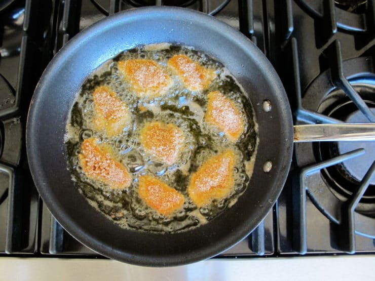 Frying chicken bites in a skillet.