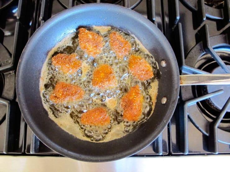 Frying chicken bites in a skillet.