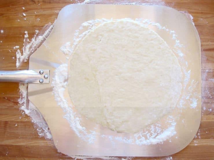 Pizza dough on a parchment sheet.