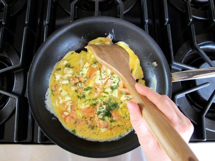Scrambling eggs in a skillet.