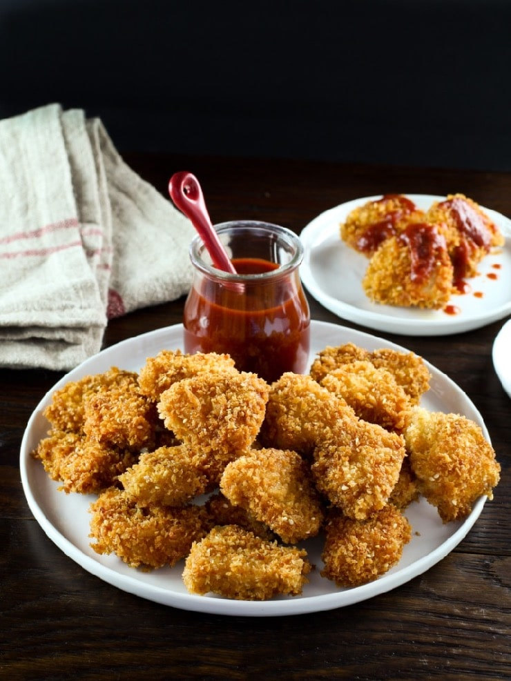 Smoky chicken schnitzel bites on plate, vertical shot, wooden table, nuggets with sauce in background.