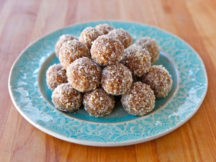 Aqua-colored plate of date truffles rolled in coconut on a wooden cutting board background.
