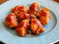Smoky Panko Schnitzel Bites with Honey Sriracha Sauce - Recipe for bite-sized chicken schnitzel pieces coated in smoky, crispy panko breadcrumbs with sesame.