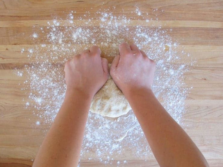Kneading pizza dough on a cutting board.