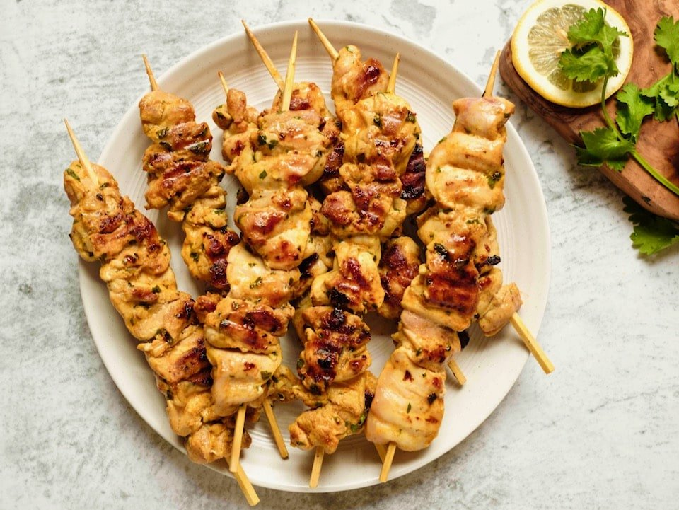 Overhead horizontal shot - plate of Lemony Marinated Chicken Skewers on countertop, lemon and parsley garnish on wooden cutting board beside the plate.